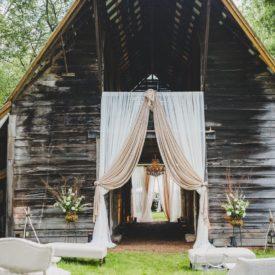 Ceremony space facing draped barn entrance.